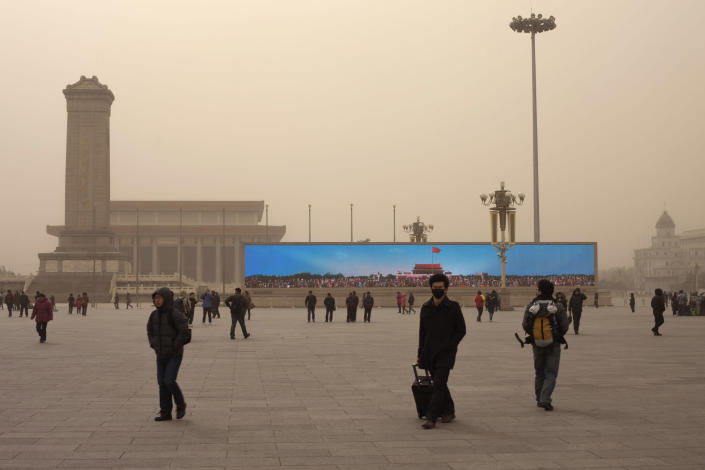 In this Feb. 28, 2013 photo, a giant electronic screen on Tiananmen Square shows an image of Tiananmen Gate under a blue sky as part of a propaganda video on a polluted day in Beijing. While the numbers are hard to quantify, executive recruitment consultants say they are noticing that it is becoming harder to attract top talent to China - both expats and Chinese nationals educated abroad. If the polluted skies continue, companies may have to fork out more money for their workers, settle for less qualified candidates or hire local workers instead of expats.(AP Photo/Alexander F. Yuan)