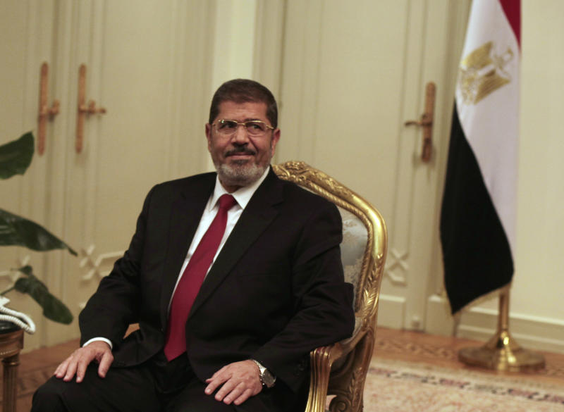 RETRANSMISSION FOR ALTERNATE CROP - Egyptian President Mohammed Morsi looks on during a photo opportunity during his meeting with Turkish Ambassador to Egypt, Hussein Awny and Turkish Foreign Minister Ahmet Davutoglu, unseen, at the Presidential Palace in Cairo, Egypt, Monday, July 2, 2012. Morsi, whose appointment is the fruit of Egypt's own uprising, said in a statement that he welcomes the opposition groups to Cairo and stressed the need for a political solution to end the crisis in Syria. (AP Photo/Maya Alleruzzo)