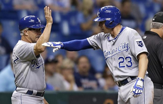 Kansas City Royals' Elliot Johnson, right, celebrates with third base coach Eddie Rodriguez after his RBI triple off Tampa Bay Rays starting pitcher Matt Moore scored Jeff Francoeur during the fifth inning of a baseball game Friday, June 14, 2013, in St. Petersburg, Fla. (AP Photo/Chris O'Meara)