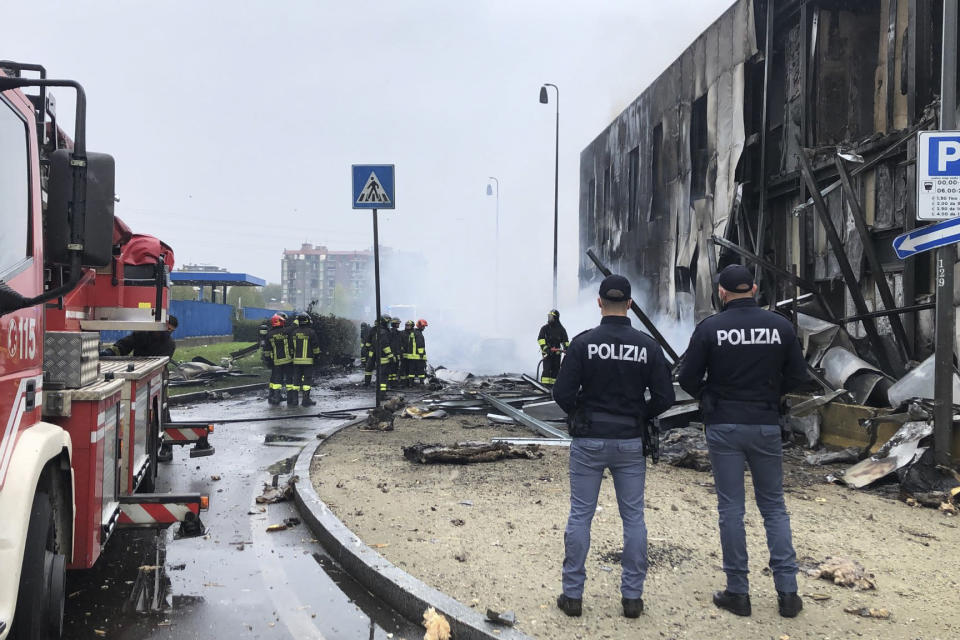 Italian police stand by as firefighters work at the site of a plane crash, in San Donato Milanese suburb of Milan, Italy, Sunday, Oct. 3, 2021. According to media reports, a small plane carrying five passengers and the pilot crashed into an apparently vacant office building in a Milan suburb. Their fates were not immediately known. (Italian Police via AP)