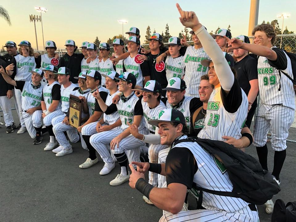 As the Lancers pose for a photo after winning the Division 2 title, Max Muncy (13) takes a seat on the knee of Roc Riggio.