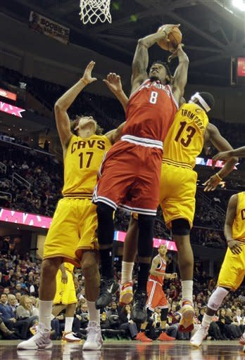 Milwaukee Bucks' Larry Sanders (8) shoots against Cleveland Cavaliers' Anderson Varejao (17), from Brazil, and Tristan Thompson (13) in the first quarter of an NBA basketball game on Friday, Dec. 14, 2012, in Cleveland. (AP Photo/Mark Duncan)