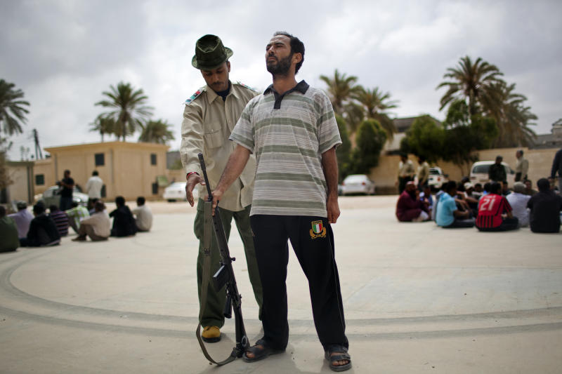 A rebel instructor tells a man how to stand in a military position during a training exercise in Misrata, Libya, Tuesday, May 24, 2011. According to rebel military authorities, after six days of military training, new recruits are ready to go to fight on the front line against Moammar Gadhafi forces. (AP Photo/Rodrigo Abd)