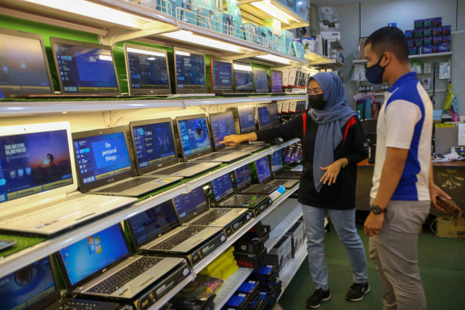A sales assistant attends to a customer at the Mytec Computer in Station 18, Pengkalan in Ipoh. — Picture by Farhan Najib