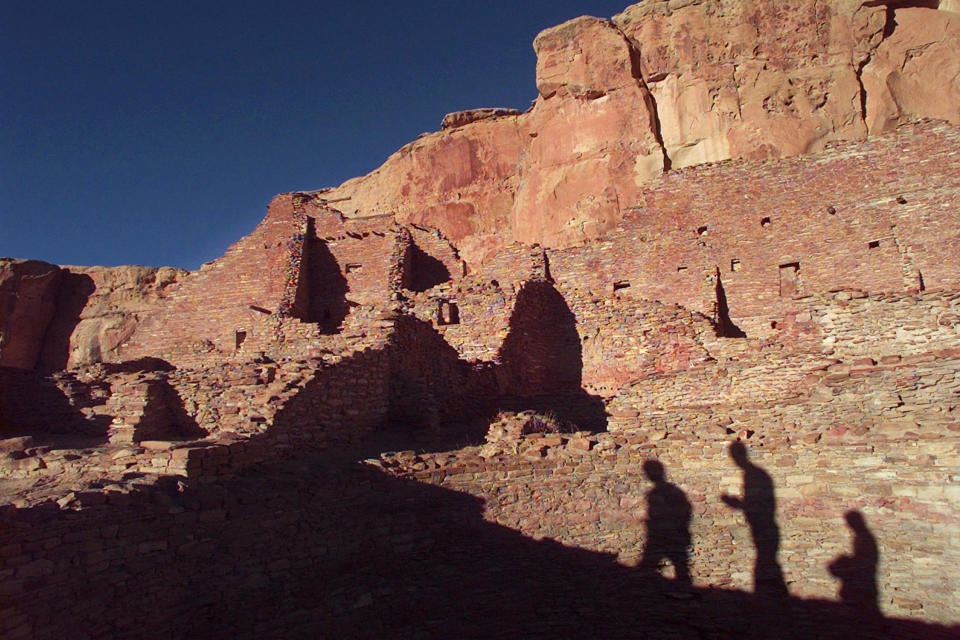 FILE - In this Nov. 21, 1996, file photo, tourists cast their shadows on the ancient Anasazi ruins of Chaco Culture National Historical Park in New Mexico. Environmentalists and Native American activists say the Biden administration's review of the federal oil and gas leasing program should result in more protections for an area of northwestern New Mexico that's considered sacred. The fight over drilling on federal land bordering Chaco Culture National Historical Park has spanned multiple presidential administrations, and an effort to update the area's management plan remains unfinished after years. (AP Photo/Eric Draper, File)
