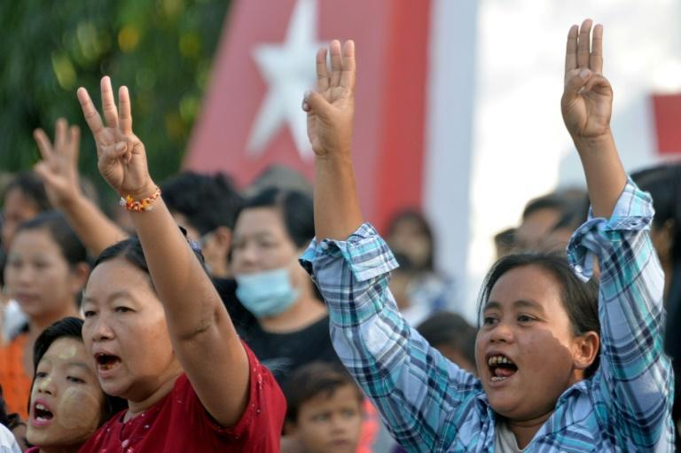 Myanmar protesters hold up the three finger salute - a symbol of resistance - at an anti-coup demo in the city of Naypyidaw