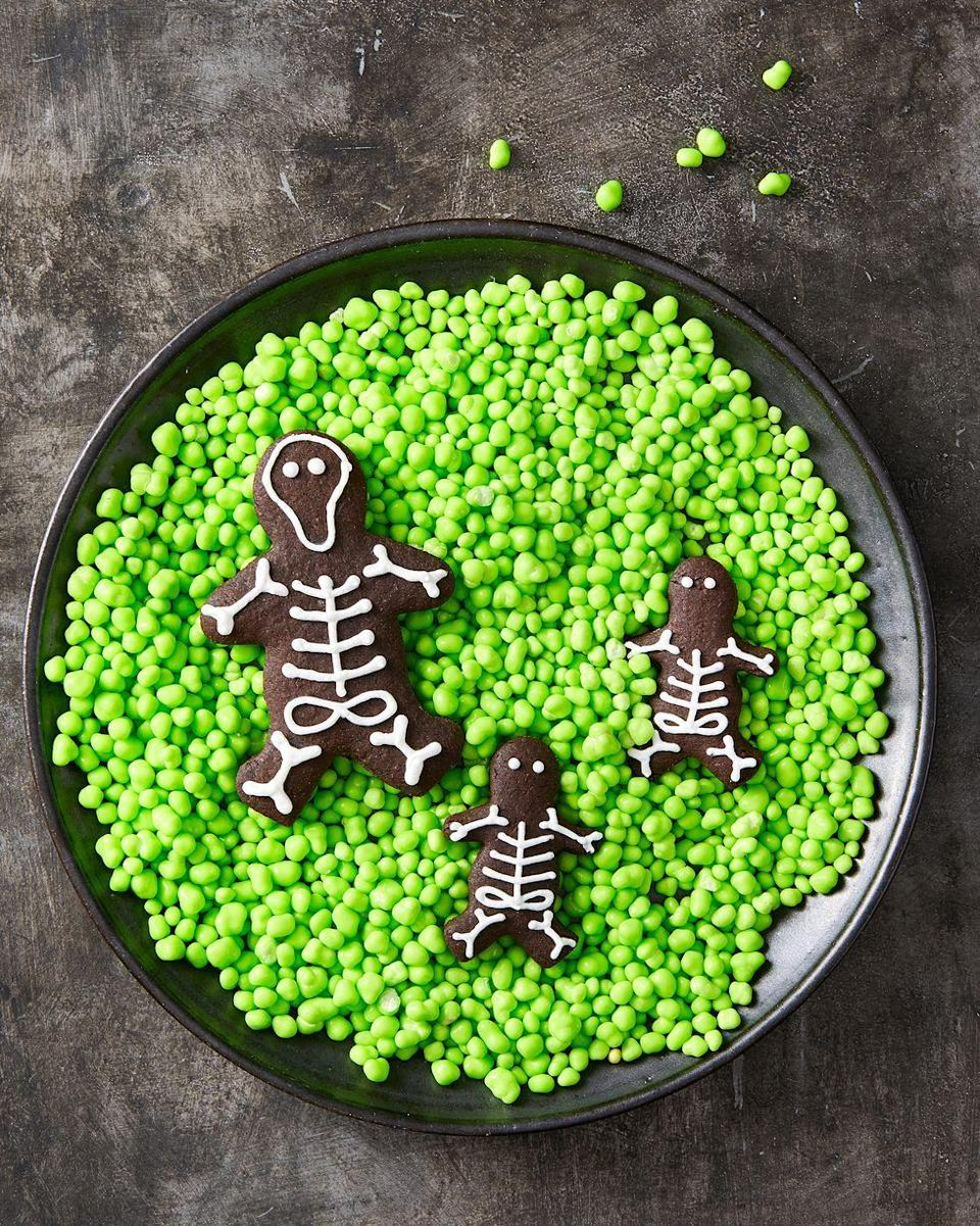 """<p>Skip gingerbread men and make this dark chocolate skeleton family using our easiest <a href=""""https://www.goodhousekeeping.com/food-recipes/a28565256/royal-icing-recipe/"""" rel=""""nofollow noopener"""" target=""""_blank"""" data-ylk=""""slk:Royal Icing"""" class=""""link rapid-noclick-resp"""">Royal Icing</a> recipe instead.</p><p><em><a href=""""https://www.goodhousekeeping.com/food-recipes/party-ideas/a28592622/chocolate-skeleton-cookies-recipe/"""" rel=""""nofollow noopener"""" target=""""_blank"""" data-ylk=""""slk:Get the recipe for Chocolate Skeleton Cookies »"""" class=""""link rapid-noclick-resp"""">Get the recipe for Chocolate Skeleton Cookies »</a></em></p>"""