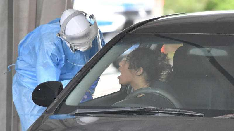 A health care worker (left) is seen testing people at a Covid-19 drive through testing clinic at Murarrie in Brisbane.