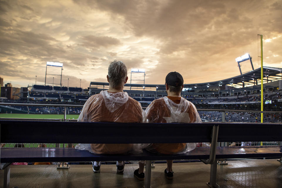 Two Texas fans watch the sun come out as the weather clears for start of the baseball game between Texas and Virginia in the College World Series Thursday, June 24, 2021, at TD Ameritrade Park in Omaha, Neb. (AP Photo/John Peterson)