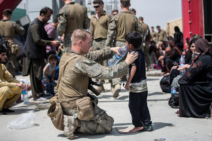 A U.S. Marine with the 24th Marine Expeditionary Unit (MEU) provides water to a child during an evacuation at Hamid Karzai International Airport, Kabul, Afghanistan, in this photo taken on August 20, 2021.  (Sgt. Samuel Ruiz/U.S. Marine Corps/Handout via Reuters)