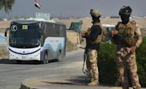 Iraqi soldiers secure buses transporting displaced families out of the shuttered camp in Habbaniyah in Iraq's Anbar province