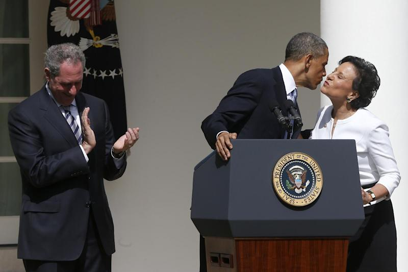 President Barack Obama leans over to kiss Penny Pritzker, his nominee for Commerce Secretary, as Michael Froman, his nominee for U.S. Trade Representative, applauds at right, Thursday, May 2, 2013, in the Rose Garden of the White House in Washington. (AP Photo/Charles Dharapak)