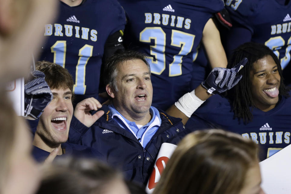 Pulaski Academy coach Kevin Kelley, center, celebrates with his team after the Arkansas Class 5A High School Championship football game on Dec. 6, 2014. (AP)