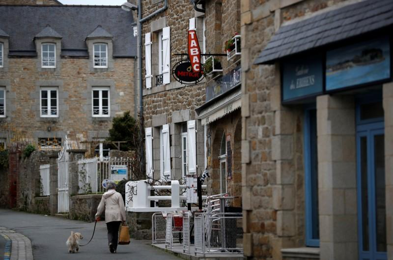 A woman walks in a street in Saint-Jacut-de-la-Mer in Brittany