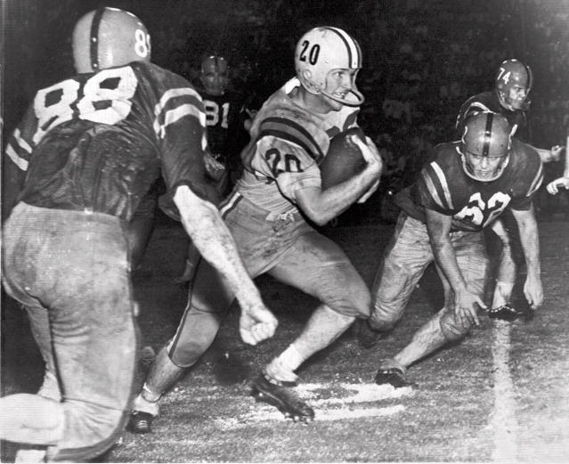 File-This this Oct. 31, 1959, file photo, Billy Cannon, Louisiana State University's All-America halfback, slips by tacklers at the start of an 89-yard punt return for a touchdown to help LSU beat third-ranked Mississippi, 7-3 in Baton Rouge, La. Cannon, the gifted running back who won the Heisman Trophy for LSU in 1959 with a memorable Halloween night punt return touchdown against Mississippi, died Sunday, May 20, 2018. He was 80. LSU said Cannon, the schools only Heisman winner, died at his home in St. Francisville, La. The cause of death was not immediately known. (AP Photo/File)