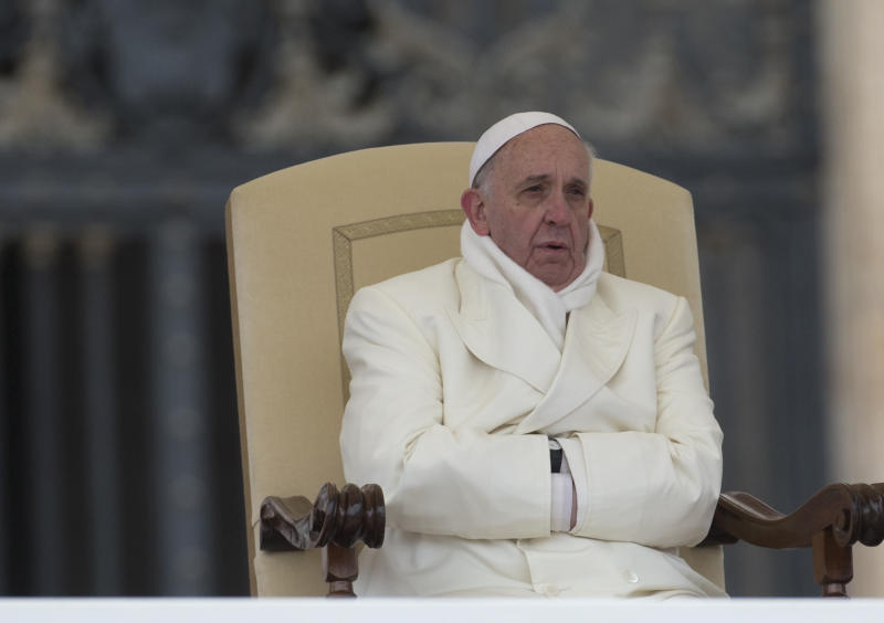 Pope Francis tries to keep himself warm as he attends his weekly general audience in St. Peter's Square at the Vatican, Wednesday, Nov. 27, 2013. Francis is bundling up for the cold snap belting Italy, donning a white double-breasted winter coat and scarf. Several times Wednesday, the pope used his sleeves as a muffler to keep his hands warm amid temperatures that dipped to freezing with the wind chill factored in. (AP Photo/Alessandra Tarantino)