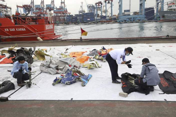 Investigators of the National Transportation Safety Committee inspect parts of aircraft's debris recovered from the Java Sea where a Sriwijaya Air passenger jet crashed, at Tanjung Priok Port, Tuesday, Jan. 12, 2021. Indonesian navy divers were searching through plane debris and seabed mud Tuesday looking for the black boxes of the Sriwijaya Air jet that nosedived into the Java Sea over the weekend with 62 people aboard. (AP Photo/Dita Alangkara)