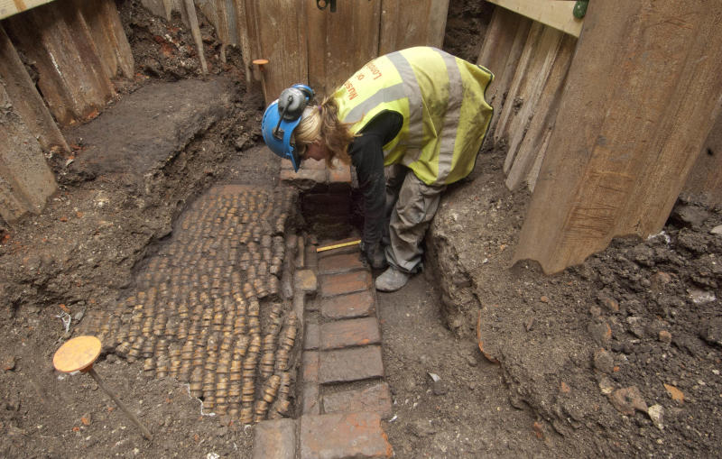 This is an image issued by Museum of London  Archaeology on Wednesday June 6, 2012 , showing  an archaeologist as she undertakes initial archaeological excavation work at the site of The Curtain Theatre in London  in October 2011. Archaeologists say they have discovered the remains of an Elizabethan theatre where some of William Shakespeare's plays were first performed. Experts from the Museum of London have uncovered a yard and gallery walls from the Curtain Theatre in Shoreditch, just east of London's business district. (AP Photo/Museum of London Archaeology)