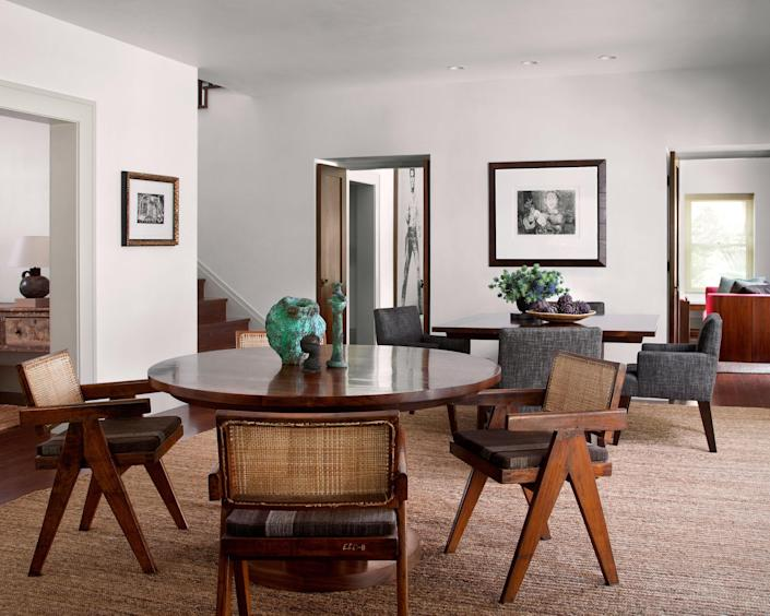 The dining room is outfitted with a pair of custom walnut tables, Pierre Jeanneret chairs with cushions made from vintage kilims, Picasso etchings, and small bronze sculptures by Harry Bertoia.