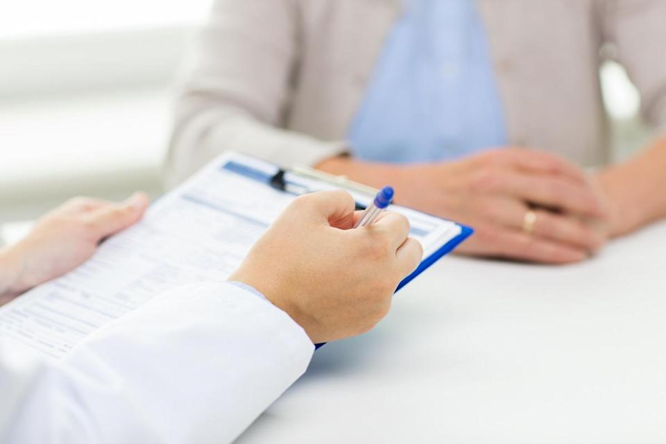 senior woman and doctor hands with clipboard meeting in medical office