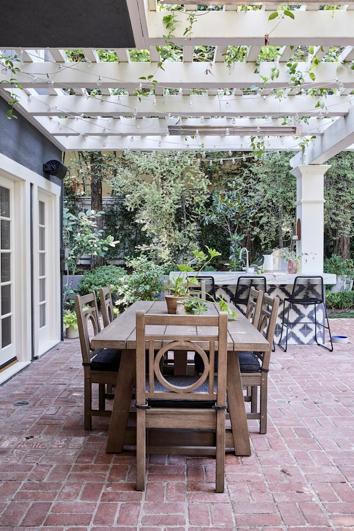 """<div class=""""caption""""> The kitchen's strong palette and expressive pattern extends to the outdoor dining area, where Duff loves to entertain family and friends. """"It's <em>always</em> a conversation starter when people come over,"""" she says. The table and chairs are from <a href=""""https://rh.com/"""" rel=""""nofollow noopener"""" target=""""_blank"""" data-ylk=""""slk:RH"""" class=""""link rapid-noclick-resp"""">RH</a>. </div>"""