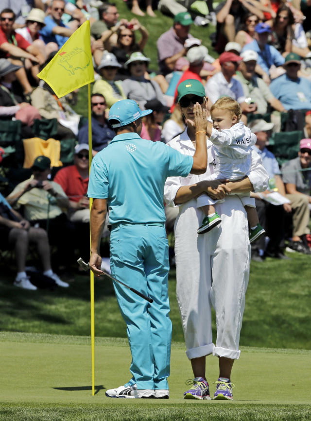 Bubba Watson's wife Angie and their son Caleb high five with Rickie Fowler during the par three competition at the Masters golf tournament Wednesday, April 9, 2014, in Augusta, Ga. (AP Photo/David J. Phillip)