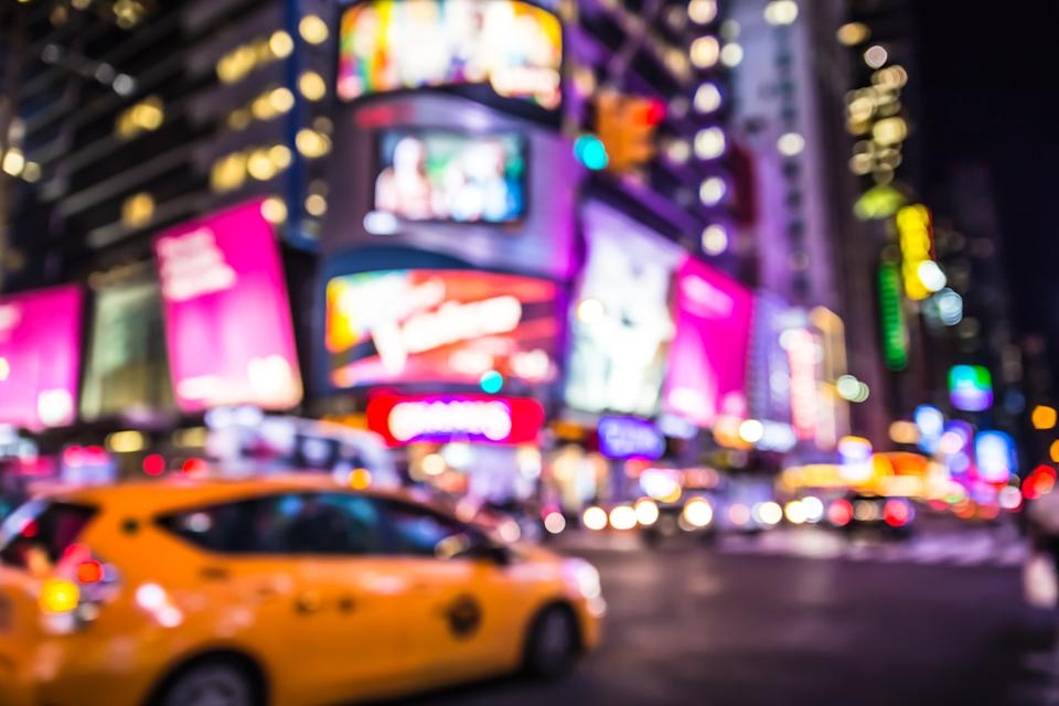 Defocused blur of Times Square in New York City with lights at night and taxi cab - Credit: littleny - stock.adobe.com