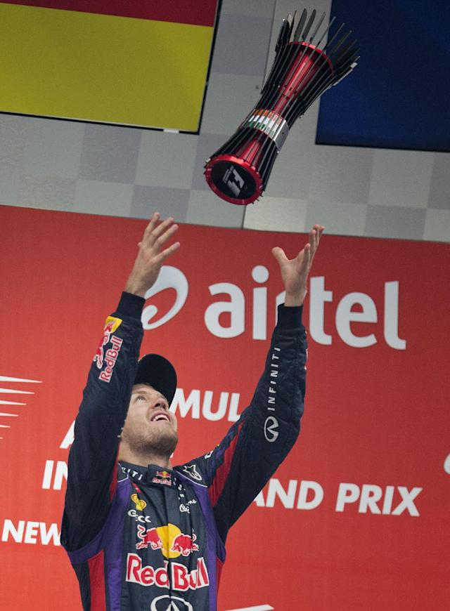 Red Bull driver Sebastian Vettel of Germany throws his trophy in the air after winning the Indian Formula One Grand Prix and his 4th straight F1 world drivers championship at the Buddh International Circuit in Noida, India, Sunday, Oct. 27, 2013. (AP Photo/Mark Baker)