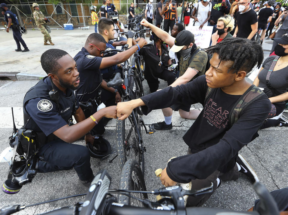"""FILE - Atlanta police officer J. Coleman, left, and protester Elijah Raffington fist bump while officers kneel down with protesters in a symbolic gesture of solidarity outside the CNN Center, Wednesday, June 3, 2020, in Atlanta during a protest sparked by the May 25 death of George Floyd in Minneapolis police custody. """"These are images from Donald Trump's America today,"""" Democratic presidential nominee Joe Biden said Thursday, Aug. 27, 2020. """"The violence we're witnessing is happening under Donald Trump. Not me. It's getting worse, and we know why."""" (Curtis Compton/Atlanta Journal-Constitution via AP, File)"""