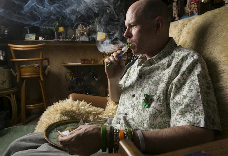 In this April 30, 2014 photo, Bill Britt, who suffers from epileptic seizures and leg pain from a childhood case of polio, vaporizes medical marijuana at his home in Long Beach, Calif. Britt lives mostly on Social Security income and gets his supply for free from a friend whom he helps water and grow the plants. Insurers are reluctant to cover medical marijuana because of conflicting laws and lack of approval from the U.S. Food and Drug Administration. (AP Photo/Damian Dovarganes)