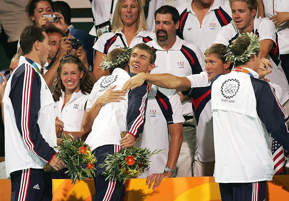 <p>Michael Phelps congratulates Ian Crocker and Jason Lezak of the United States relay team that won the gold medal in the 4 x 100-meter medley relay competition on August 21, 2004. Phelps did not swim in the final but received a gold medal for swimming the relay in the preliminaries. (Shaun Botterill/Getty Images)</p>
