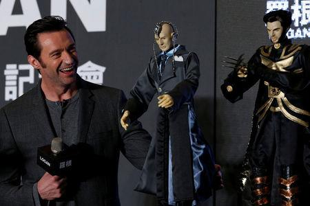 Actor Hugh Jackman poses with cloth puppets, a traditional type of opera during a news conference during Asian premiere of the X-Men series film 'Logan' in Taipei, Taiwan