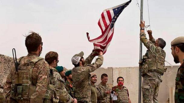 PHOTO: A U.S. flag is lowered as American and Afghan soldiers attend a handover ceremony from the U.S. Army to the Afghan National Army, at Camp Anthonic, in Helmand province, southern Afghanistan, May 2, 2021. (Afghan Ministry of Defense Press Office via AP)