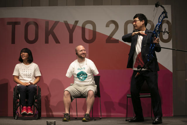Joined by Paralympian Monika Seryu, left, and comedian Ryota Yamasato, armless archer Matt Stutzman attends an event held to unveil tickets for the Tokyo 2020 Olympics and Paralympics Wednesday, Jan. 15, 2020, in Tokyo. Stutzman has become famous and known as the Armless Archer. Stutzman won a silver medal in the 2012 London Paralympics and will be among the favorites in archery this year in Tokyo. (AP Photo/Jae C. Hong)