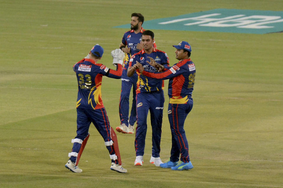Karachi Kings Arshad Iqbal, center, celebrates with teammates after taking the wicket of Quetta Gladiators Azam Khan during a Pakistan Super League T20 cricket match between Karachi Kings and Quetta Gladiators at National Stadium, in Karachi, Pakistan, Saturday, Feb. 20 2021. (AP Photo/Fareed Khan)