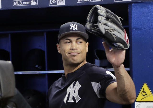 New York Yankees left fielder Giancarlo Stanton waves as he walks into the dugout before a baseball game against the Miami Marlins, Tuesday, Aug. 21, 2018, in Miami. Stanton says it's weird to return to Miami, where he played his first eight major league season and will now try to help the Yankees beat the Marlins. (AP Photo/Lynne Sladky)