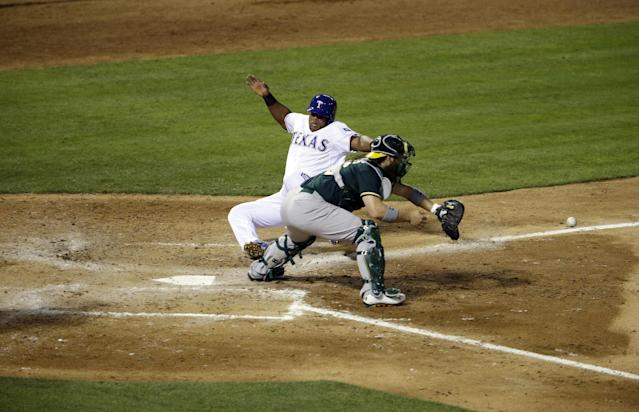 Oakland Athletics catcher Derek Norris reaches out for the throw as Texas Rangers' Adrian Beltre, left, scores on double by Alex Rios a double in the fourth inning of a baseball game, Tuesday, April 29, 2014, in Arlington, Texas. (AP Photo/Tony Gutierrez)