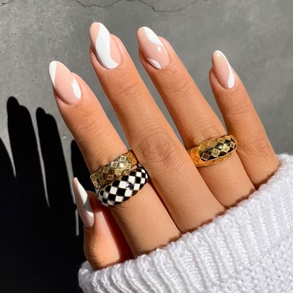 """<p>Swirls are the ultimate amalgamation of 2021's <a href=""""https://www.allure.com/story/nail-trends-2021?mbid=synd_yahoo_rss"""" rel=""""nofollow noopener"""" target=""""_blank"""" data-ylk=""""slk:top nail trends"""" class=""""link rapid-noclick-resp"""">top nail trends</a>. They're a throwback design with minimal graphics <em>and</em> negative space. Best of all, Amy Le says you can easily execute swirl nails yourself — no matter how skilled you may be in the nail art department. </p> <p>Plus, swirls suit <em>everyone</em>. """"They look good on any nail length and nail shape,"""" Le tells <em>Allure</em>. """"If you're reading this right now, swirls work on your nails, too. Trust me.""""</p> <p>All three of Le's whirly wonders require two tools: nail polish and a striping brush. """"You don't need anything expensive,"""" Le says. """"A simple Amazon search of 'nail art brushes' works."""" An ultra-fine eyeliner brush works, too. Just be sure to clean it off with nail polish remover before throwing it back into your makeup bag.</p> <p>For this neutral, low-key take on the trend, Le started off by prepping her nails with a base coat (the Best of Beauty-winning <a href=""""https://shop-links.co/1742875044144557457"""" rel=""""nofollow noopener"""" target=""""_blank"""" data-ylk=""""slk:Sally Hansen Color Therapy Beautifiers Strengthening Base Coat"""" class=""""link rapid-noclick-resp"""">Sally Hansen Color Therapy Beautifiers Strengthening Base Coat</a> is an <em>Allure</em>-editor favorite) and a pinky-nude, like the <a href=""""https://dearsundays.com/product/nail-polish/colors/l-06/?utm_source=narrativ"""" rel=""""nofollow noopener"""" target=""""_blank"""" data-ylk=""""slk:Sundays Nail Polish in L.06"""" class=""""link rapid-noclick-resp"""">Sundays Nail Polish in L.06</a>. Next, the handy striper brush was dipped into a <a href=""""https://www.allure.com/gallery/best-white-nail-polish?mbid=synd_yahoo_rss"""" rel=""""nofollow noopener"""" target=""""_blank"""" data-ylk=""""slk:white lacquer"""" class=""""link rapid-noclick-resp"""">white lacquer</a> before she painted a squiggly line onto the corner"""