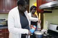 Ebele Azikiwe, 12, right, cooks with her mother, Rume Joy Azikiwe-Oyeyemi, at home in Cherry Hill, N.J., Wednesday, March 24, 2021. Ebele testified in October at state Assembly hearing, lending her support to legislation requiring New Jersey's school districts to add diversity to curriculums. Democratic Gov. Phil Murphy signed the bill into law. (AP Photo/Matt Rourke)