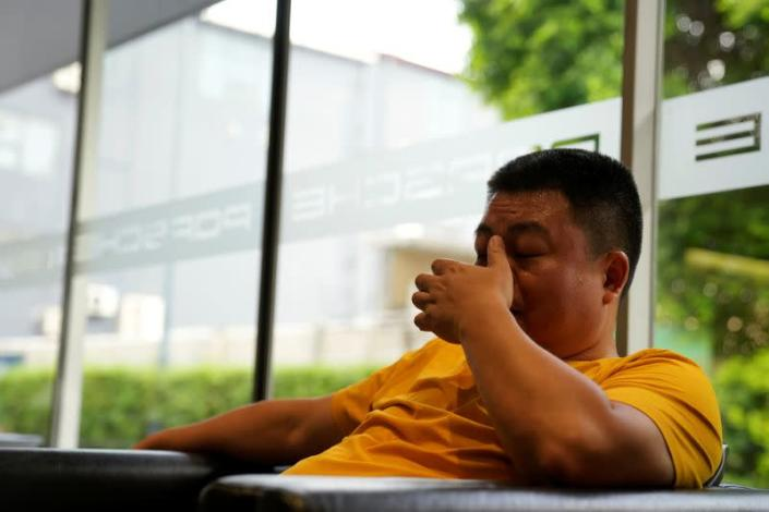 Guo Hui reacts as he waits at a car dealership to sell his Porsche Cayenne in order to pay his debts, in Guangzhou