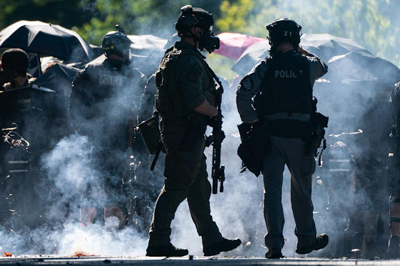 Firecrackers go off near members of a police SWAT team during protests in Seattle. Source: Getty Images