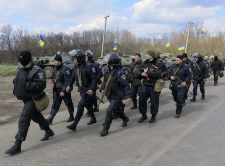 Members of the Ukrainian Interior Ministry walk past armored personnel carriers at a checkpoint near Izium