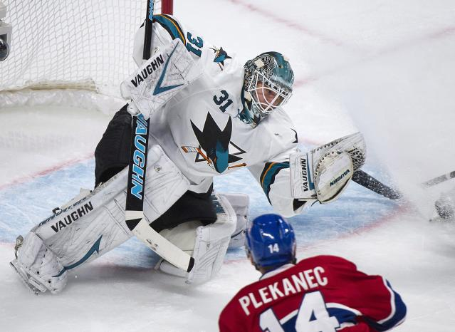 San Jose Sharks goaltender Antti Niemi makes a save against Montreal Canadiens' Tomas Plekanec during the first period of an NHL hockey game in Montreal, Saturday, Oct. 26, 2013. (AP Photo/The Canadian Press, Graham Hughes)