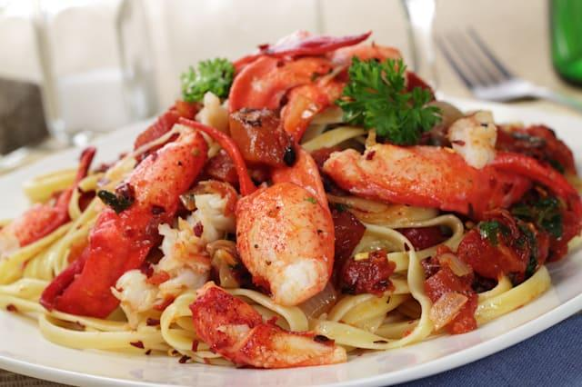 A plate of fettuccine pasta with Lobster and Fire roasted tomatoes in a spicy red pepper flake sauce