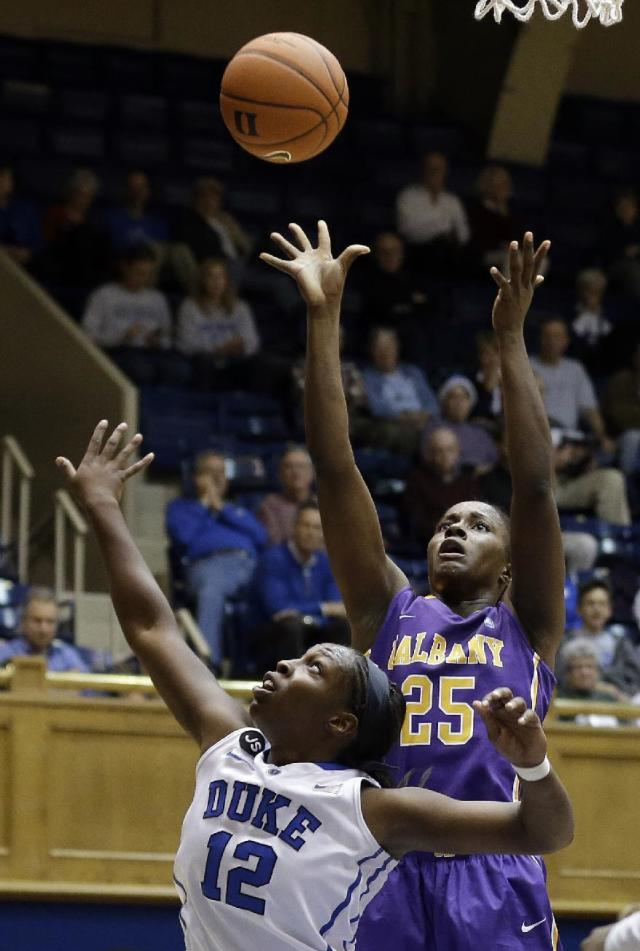 Duke's Chelsea Gray (12) defends as Albany's Shereesha Richards (25) shoots during the second half of an NCAA college basketball game in Durham, N.C., Thursday, Dec. 19, 2013. Duke won 80-51. (AP Photo/Gerry Broome)