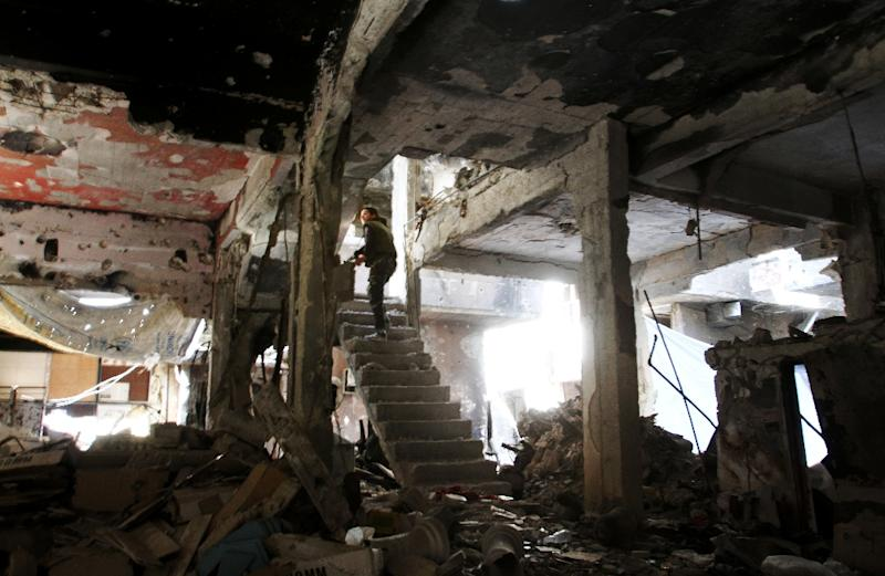 A man stands on a staircase inside a demolished building in the Yarmuk Palestinian refugee camp in the Syrian capital Damascus in April 2015 (AFP Photo/YOUSSEF KARWASHAN, -)