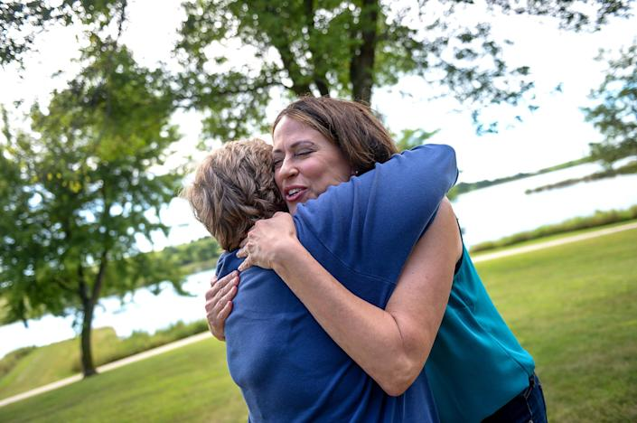 Theresa Greenfield hugs an attendee at a Democratic Party picnic this past August. Everywhere she goes, people come forward with their own stories about Social Security, the candidate said. (Photo: Caroline Brehman/Getty Images)
