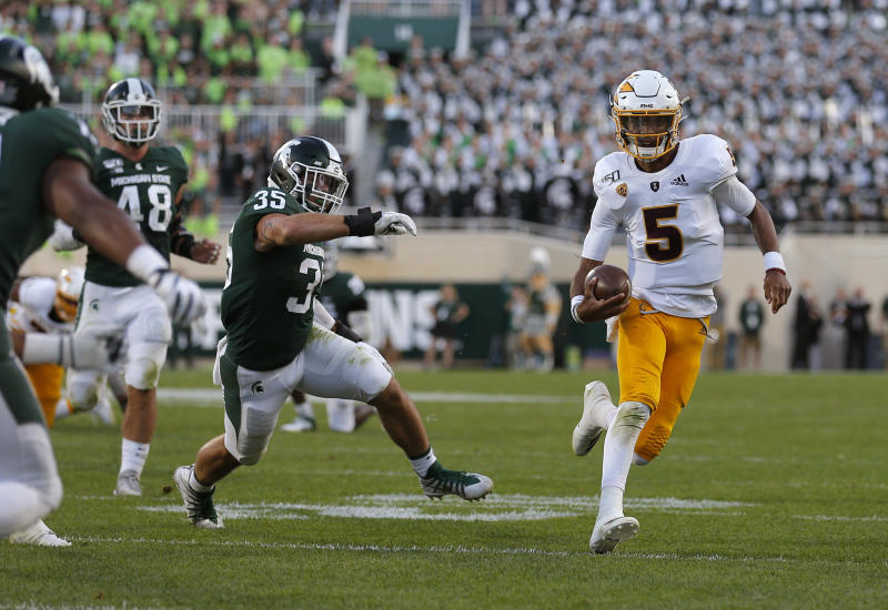 Arizona State quarterback Jayden Daniels, right, scrambles for a first down against Michigan State's Joe Bachie (35) and Kenny Willekes (48) late in the fourth quarter of an NCAA college football game, Saturday, Sept. 14, 2019, in East Lansing, Mich.  (AP Photo/Al Goldis)