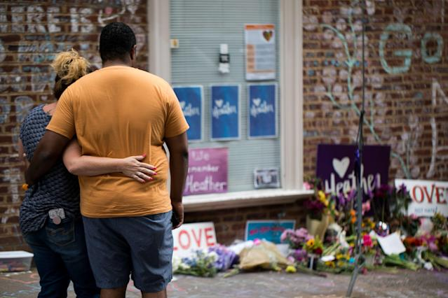 <p>A couple comforts each other as they observe the flowers and hand-written messages at a makeshift memorial dedicated to Heather Heyer off the mall in downtown Charlottesville, Va., one-year after the violent white nationalist rally when Heyer was killed and dozens of others injured. (Photo: Logan Cyrus/AFP/Getty Images) </p>