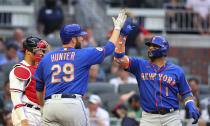 New York Mets' Jonathan Villar, right, is greeted by Tommy Hunter hitting a two-run home run, next to Atlanta Braves catcher William Contreras during the third inning of a baseball game Tuesday, May 18, 2021, in Atlanta. (Curtis Compton/Atlanta Journal-Constitution via AP)